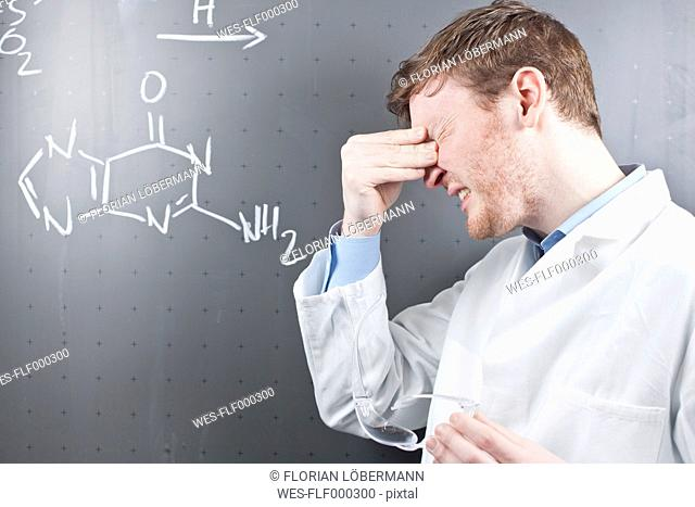 Germany, Young scientist with serious facial expression and chemical equation on chalk board