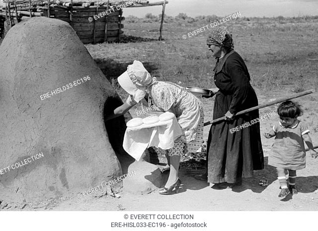 Two Spanish-American women placing loaves of bread in outdoor earthen oven for baking, Taos County, New Mexico