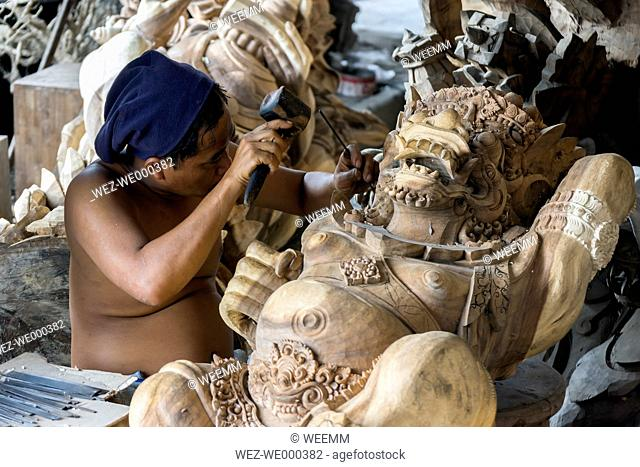 Indonesia, Bali, Ubud, Traditional wood carver's workshop with man working on religious wood sculptures