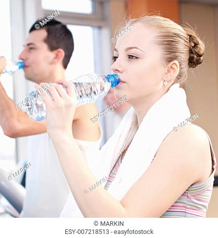 Man and woman drinking water after sports. Fitness gym