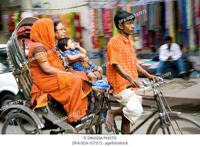 Cycle Rickshaw Rider with Passengers ;  traffic at Dhaka ; Bangladesh