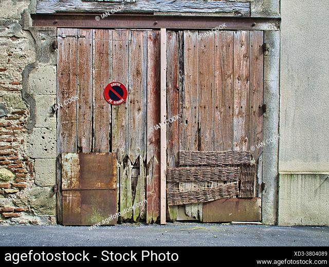 old rotting garage door, Casseneuil, Lot-et-Garonne Department, Nouvelle-Aquitaine, France