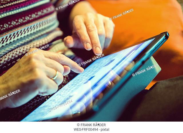 Senior woman using tablet at home, close-up