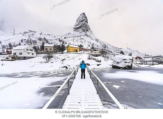 Woman standing on a wooden bridge under the snow, looking towards Hammarskaftet peak. Reine, Nordland county, Northern Norway, Norway