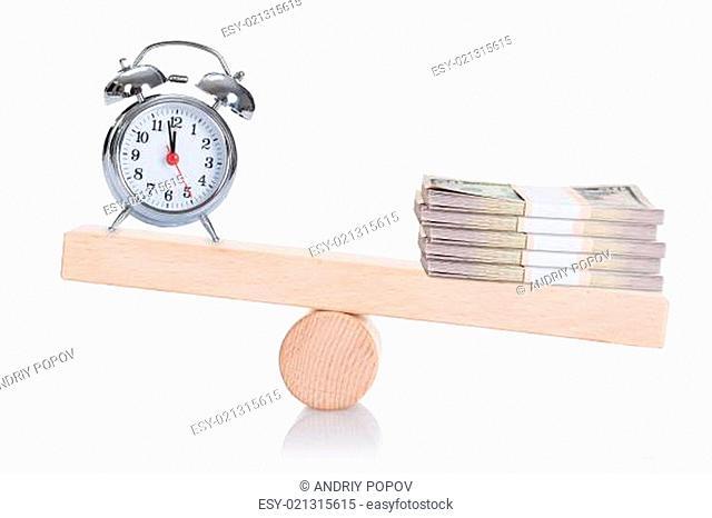 Alarmclock And Stacked Dollar Bundles Balancing On Seesaw