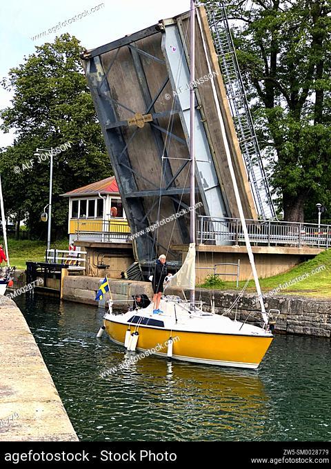 A sailing boat pass an open bridge in Gota canal at Motala, Östergötland, Sweden