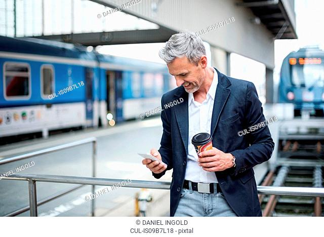 Mature businessman looking at smartphone on train station platform