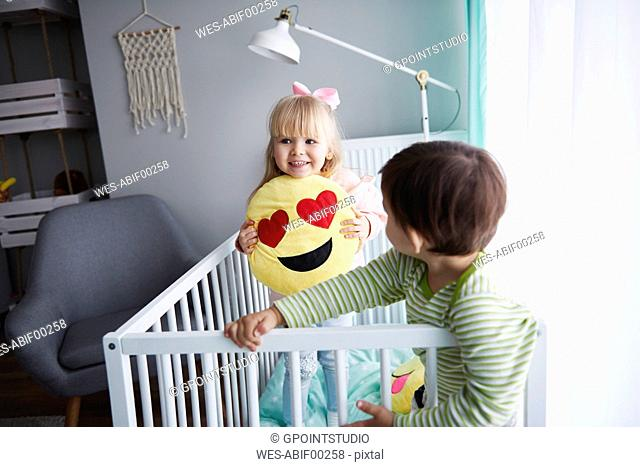 Portrait of smiling little girl standing in crib with her brother in the foreground