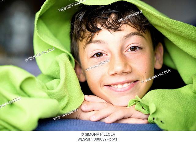 Portrait of smiling boy under a green blanket