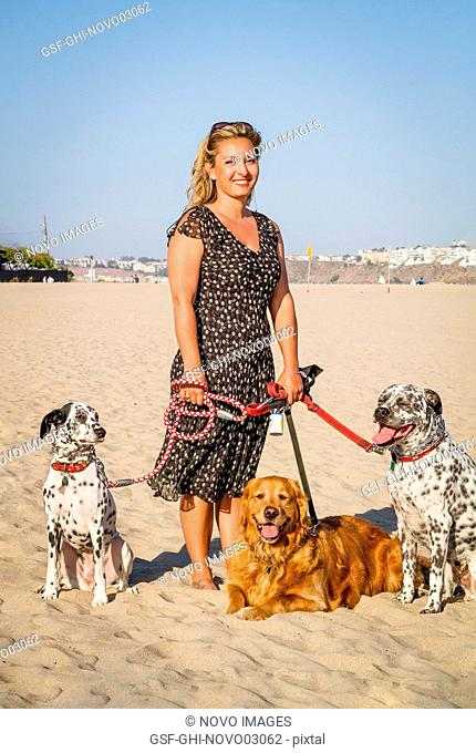 Portrait of Woman with Three Dogs on Beach