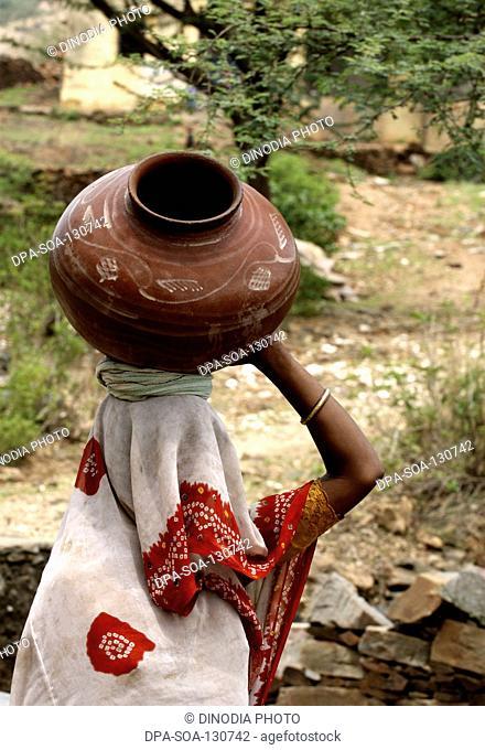 Woman carrying water in earthen pot ; Dilwara town ; Rajasmand district ; Rajasthan ; India