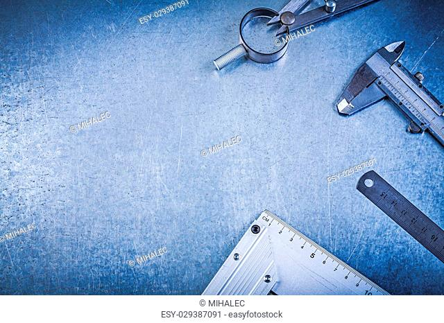 Metal construction drawing compass ruler vernier caliper try square on metallic background