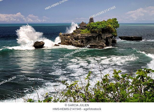Indonesia, Nusa Tenggara, Bali, Tabanan, wave crashing on Pura Tanah Lot, large rock with a Hindu temple in the ocean