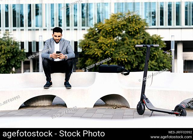 Casual young businessman sitting on a bench in the city using cell phone