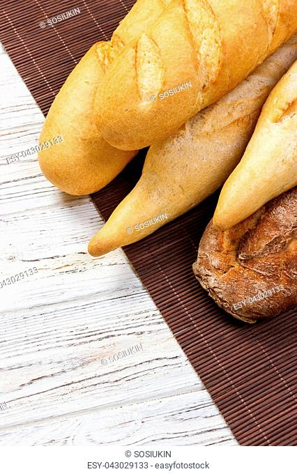 Loaf of bread on a white rustic table. baguette loaf