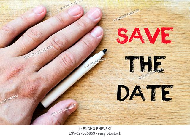 Human hand over wooden background and save the date text concept