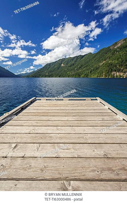 Wooden pier leading to lake