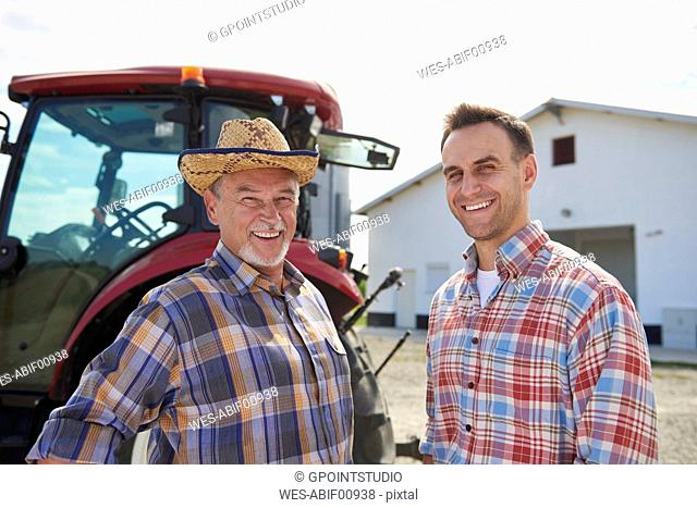 Portrait of two farmers in front of the barn