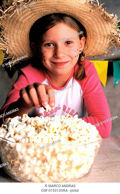 a blond girl eating popcorn