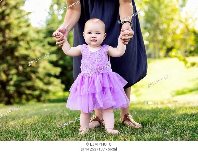 A mother teaching her baby daughter how to walk in a city park on a warm fall afternoon: Edmonton, Alberta, Canada