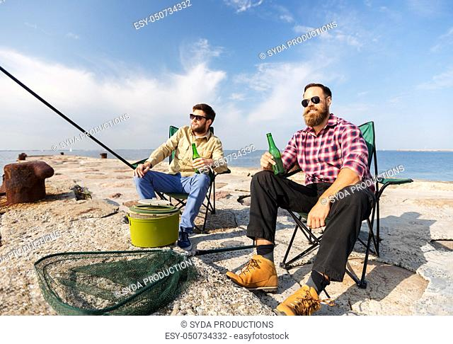 male friends fishing and drinking beer on sea pier
