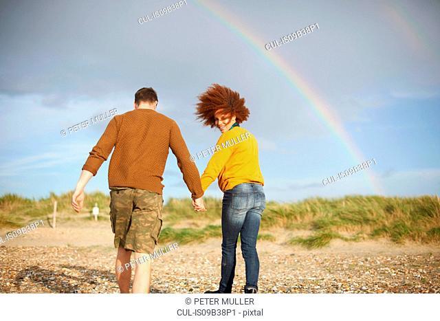 Couple walking on beach towards rainbow