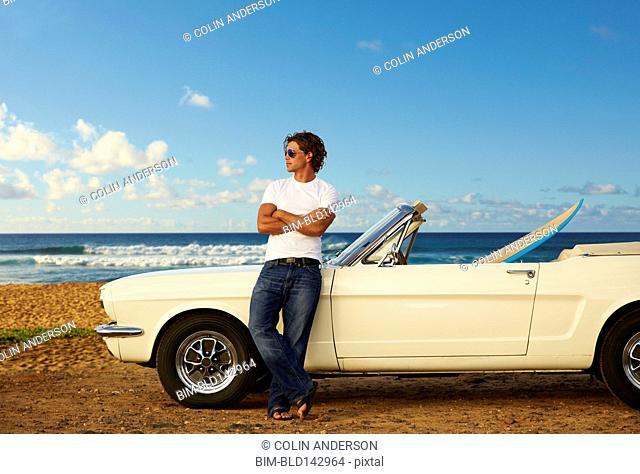 Caucasian man relaxing on convertible on beach