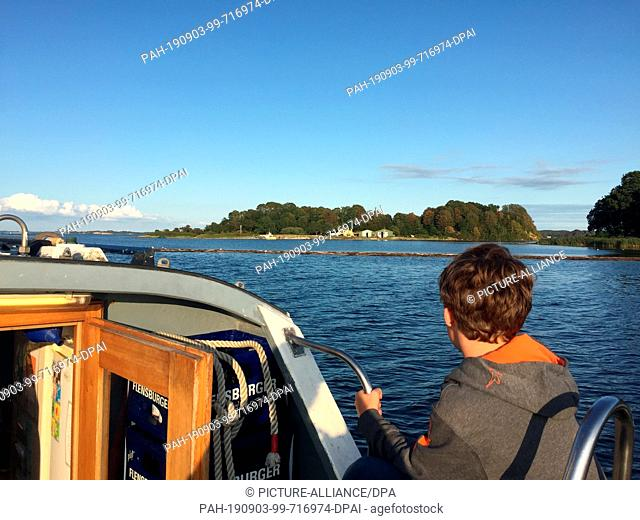 "21 August 2019, Schleswig-Holstein, Flensburg: A passenger sits on board the excursion ship """"Flora II"""", in the background you can see the Danish ox islands"