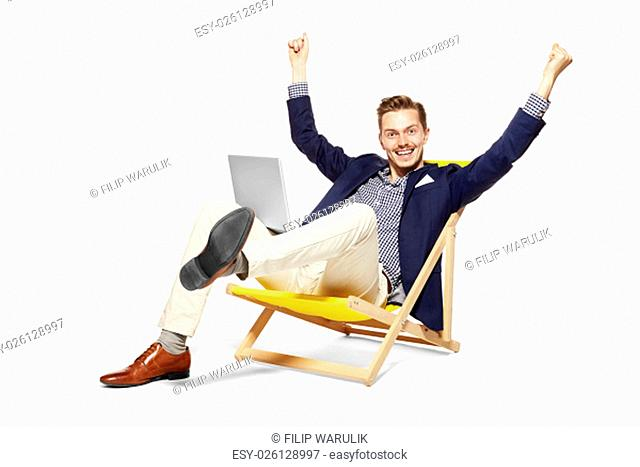 Concept shot of satisfied young man sitting on sunbed. He raises his arms in a gesture of victory