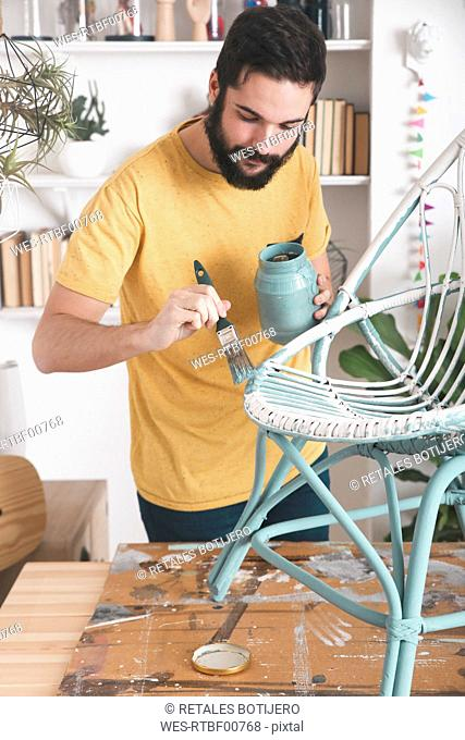 Bearded man painting wicker armchair at home