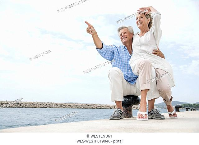 Spain, Senior couple at harbour, smiling