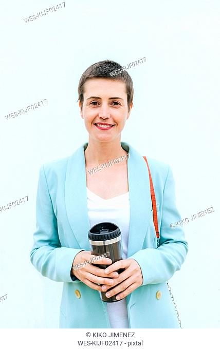 Woman wearing suit jacket with thermo mug in front of white wall