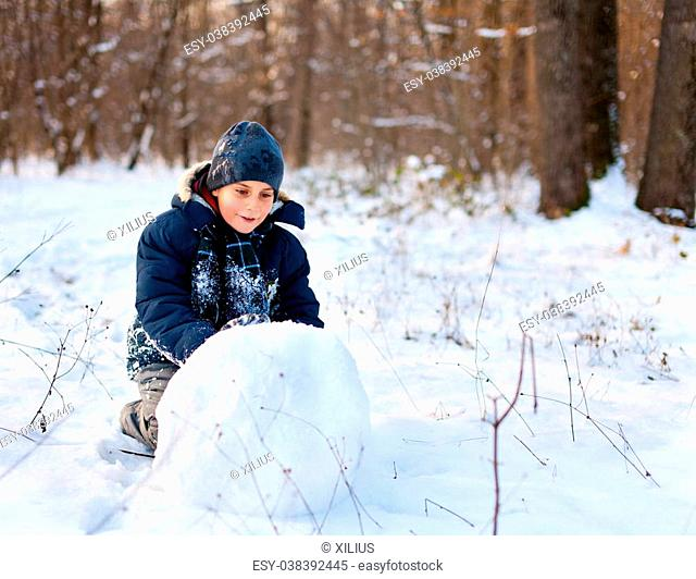 Happy kid playing in the snow near a forest