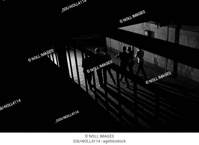 Group of Men Walking Through Dark Corridor