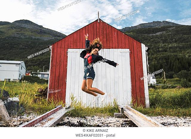 Young woman jumping in front of red barn in Nothern Norway