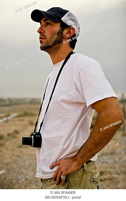 Man with digital camera looking out at desert storm clouds, Las Vegas, Nevada, USA
