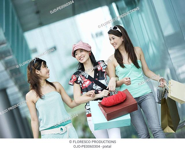 Three women outdoors with shopping bags