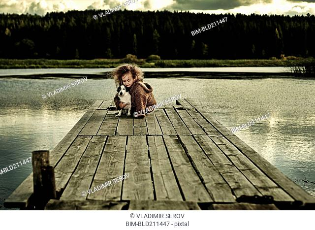 Caucasian girl with dog on wooden deck in still lake