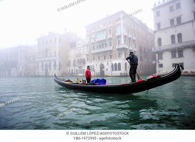 A Gondola sailing along the Grand canal of Venice covered with thick fog, Italy