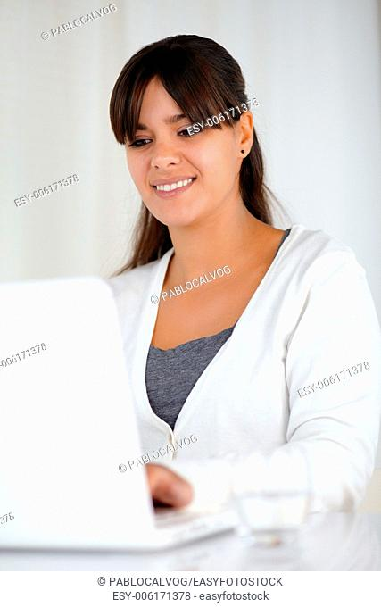Portrait of a smiling young female working with laptop computer
