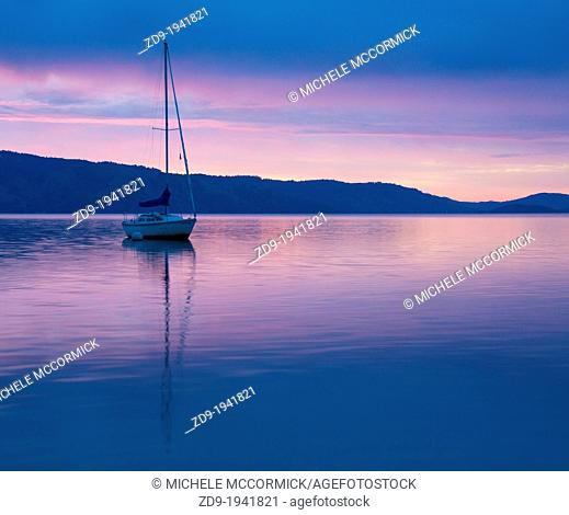 A sailboat is reflected in the dawn glow on California's Clear Lake