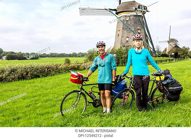 Female and male cyclists on grassy hill with two old wooden windmills in the background, near Stompwijk; Netherlands