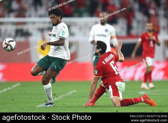 11 February 2021, Qatar, Ar-Rayyan: Al Ahly's Yasser Ibrahim (R) and Palmeiras' Luiz Adriano battle for the ball during the FIFA Club World Cup Third Place...