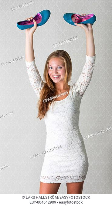 Beautiful young adult female holds a pair of blue high heel shoes in her raised hands