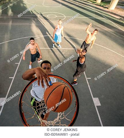High angle view of friends on basketball court scoring basketball hoops
