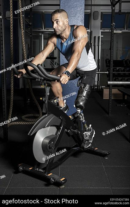 Confident athletic man with artificial leg limb riding stationary bicycle in gym