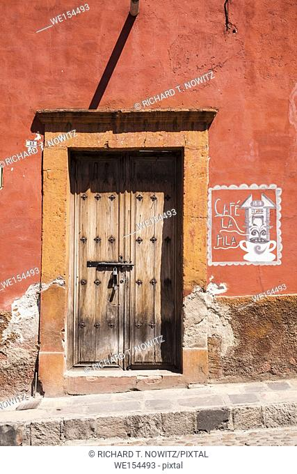 Traditional adobe house with old wooden door in historic center of Guanajuato, Mexico