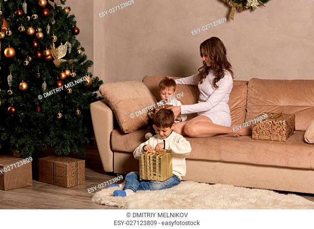Happy family with gift boxes are sitting on a sofa near Christmas tree at home. Merry Christmas and Happy New Year. Beautiful young mother with two sons