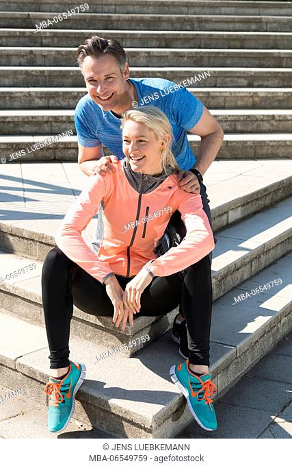 Couple in sportswear sitting on stairs
