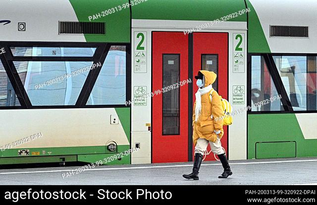 13 March 2020, Thuringia, Erfurt: A woman with a face mask walks along a platform at Erfurt main station. The local and long-distance rail traffic of the...